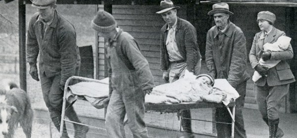 Four men carry a person on a metal frame bed out of a building, a nurse carrying a baby follows.