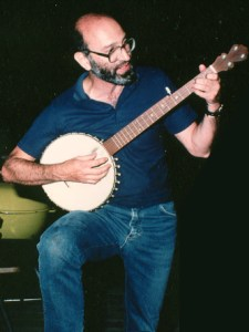 A man in jeans playing a banjo.