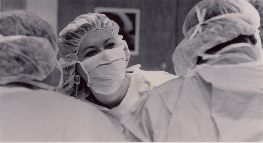 A Native American woman in scrubs and a mask does surgery