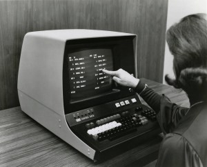 A woman touches the screen of an early data entry terminal.