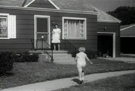 A young white girl runs toward a white woman standing at the front door of a house.