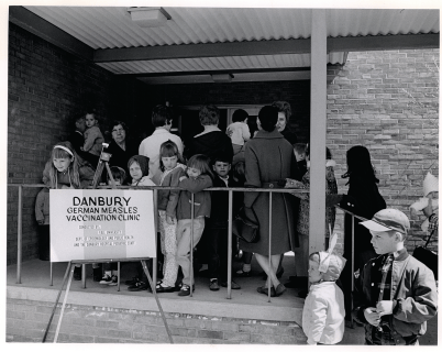 White children and adults wait in line for vaccinations