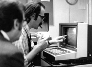 A white man touches the screen of an early data entry terminal while another looks on.