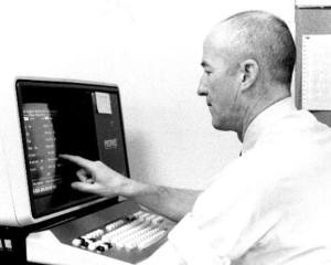 A white man touches the screen of an early data entry terminal.