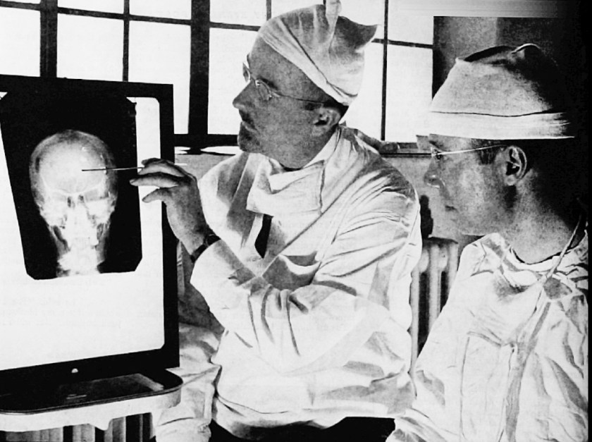 Two men in surgeons clothes look at an X-ray.
