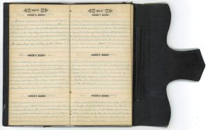 An opened notebook with preprinted dates filled in with pencil.