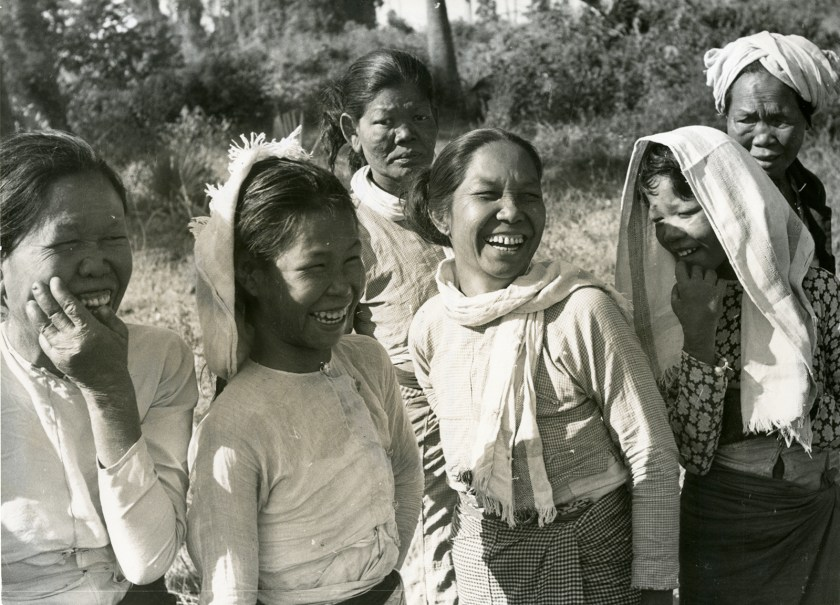 Six women, some smiling, watch a celebration honoring the success of an anti-leprosy campaign in Burma (now Myanmar)