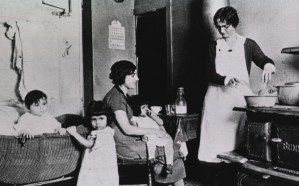 A nurse stands at a stove demonstrating proper baby bottle sterilization techniques to a woman seated nearby with a child sitting on her lap.