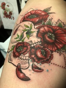 A photograph of tattoo in color featuring a skull and poppies.