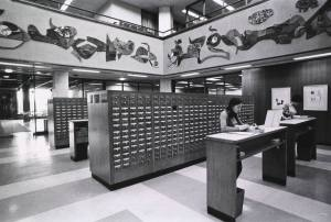 Two women stand at counters looking at drawers of cards removed from the card catalog.