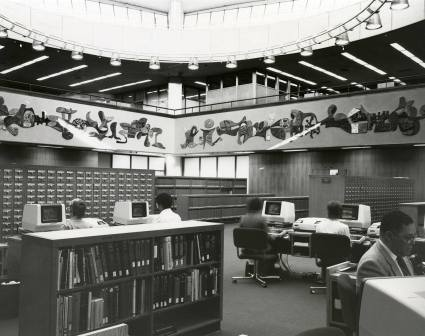 People sit at computer terminals on tables next to the card catalogs and bookshelves.