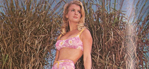 Detail of a color magazine photo of a blond woman in a pink bikini.