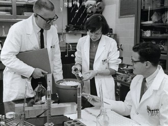 A white woman and two white men do lab science