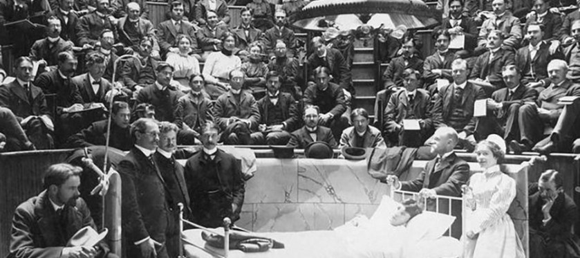 A doctor and nurse stand at thehead of a patient bed in a large amphetheater full of people.
