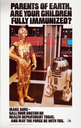 Image shows R2-D2 and C3PO from the film Star Wars standing and surrounded by monitors and flashing equipment