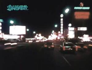 A still from a film showing a city street at night with many lit signs and billboards.
