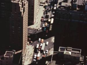 Still from a film showing an aerial view of a busy city street.