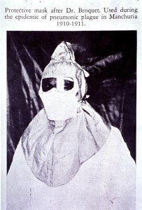 A figure in a gown and full head and sholders mask with goggles.