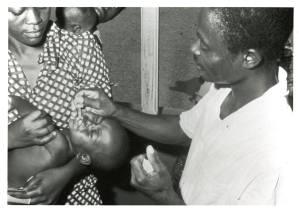 A black man drops a liquid into an infant's mouth.