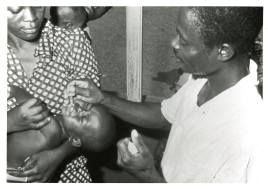 A black man drops a liquid into an infant's mouth.