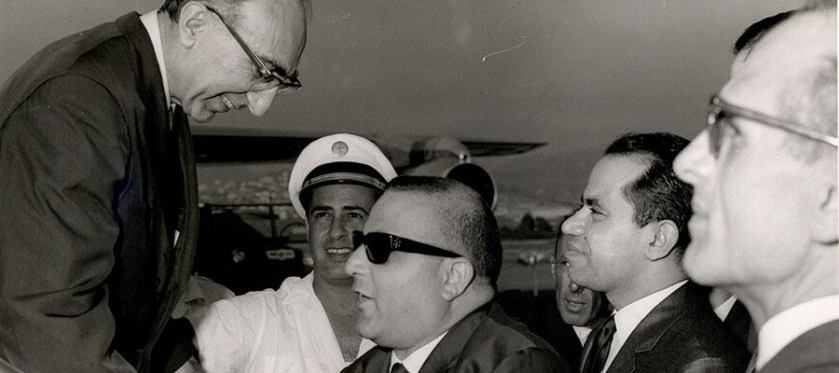 Men in suits greet DeBakey as he leaves a plane.