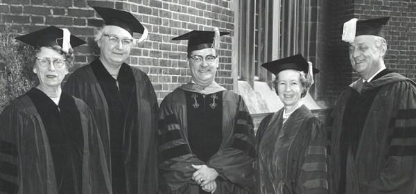 Two men and three women pose in academic regalia.
