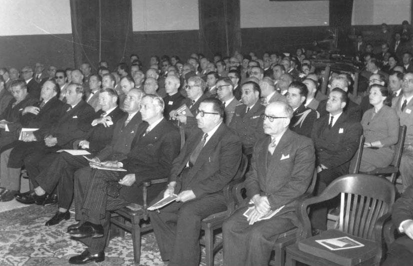 A large audience of men in suits sit in chairs.