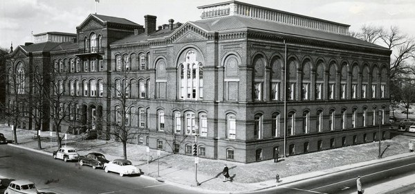 A photograph of a corner view of a large building occupying a city block.