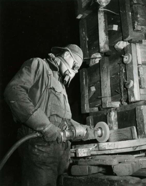 A man wearing goggles, a respirator, and heavy gloves is using a mechanical power driven grinding wheel.