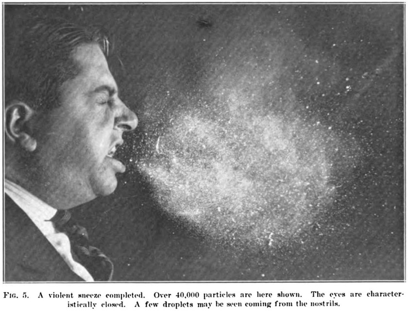 A photograph of a man sneezing.
