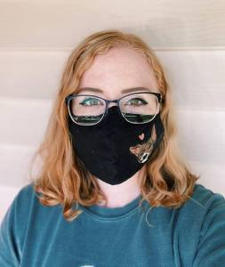 A young woman in a cloth mask and glasses.