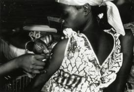 A black woman recieves an injection in her arm.