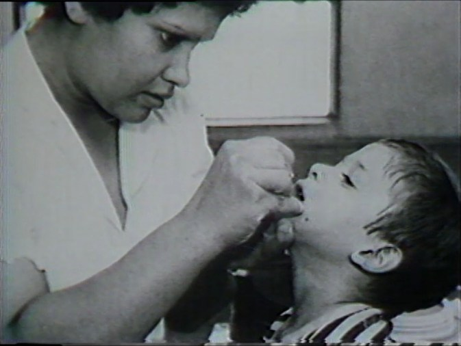 A woman carefully puts something in a childs mouth..