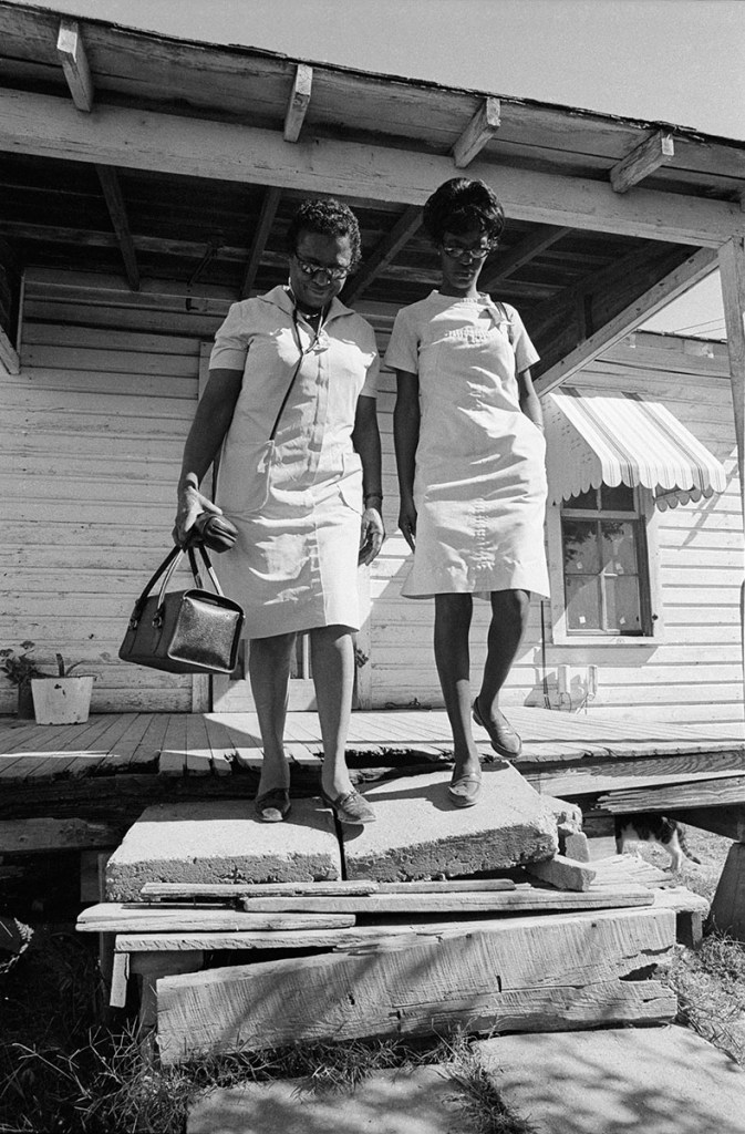 Two Black wormin in white uniforms leave a house over broken concrete.