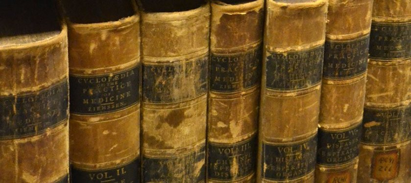 Leather bound books on library shelving showing considerable deterioration with discoloration, roughness and separation.
