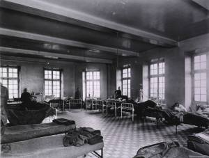 A large open tiled room with high windows and cots along all the walls, patients and staff look at the camera.