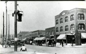 A city street with building, cars, trucks, Electrical Poles in the foreground and people walking and sitting on the curb.
