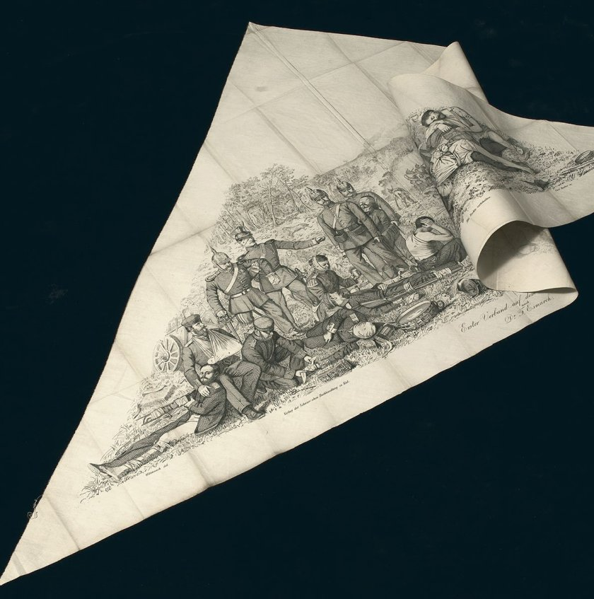 A triangle of cloth with a printed image of a realisticly rendered scene of injured soldiers bandaged in various ways.