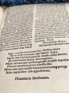 A page of a book in Latin, the page is printed in two columns with a full width poem of 8 ines at the end.