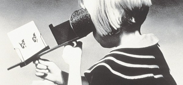 A girl sitting at a desk holds a stereoscope with a card in it up to her face.