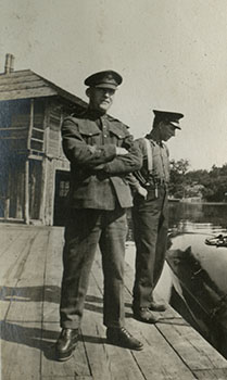 Two men in uniform stand on a dock.