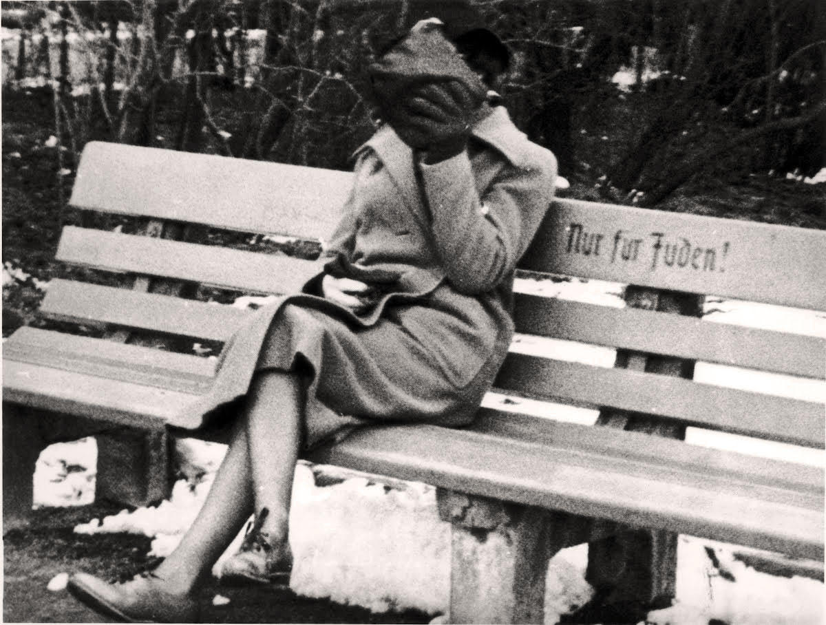 pinterest.com. A Jewish woman who is concealing her face sits on a park bench marked 'Only for Jews'. Austria, 1938