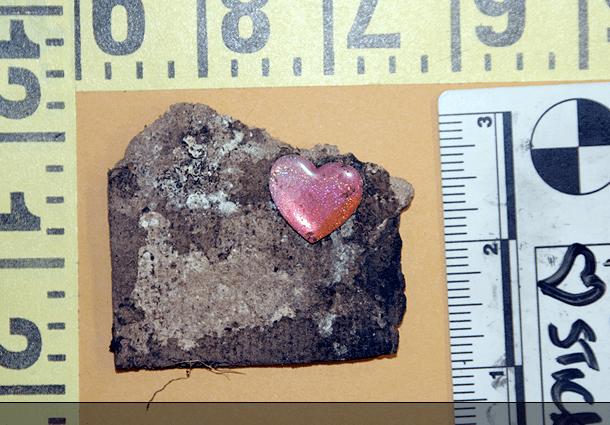 Heart sticker found at burial/dump scene.