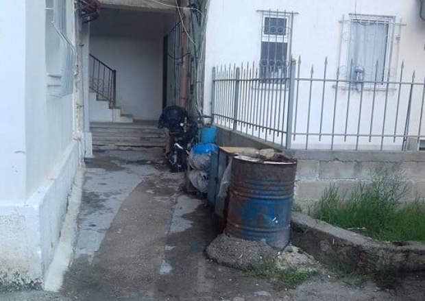 Pompa poshtë dritareve të banesave në katet e para në një lagje të Fierit. Foto: Gëzim Hoxha