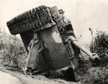 Un soldat britannique se protège de la pluie sous un char Tigre en Italie, 1944
