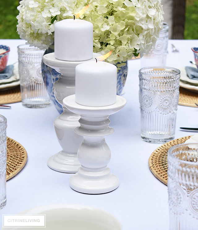 Vintage inspired outdoor late summer tablescape with white pillar candleholders.