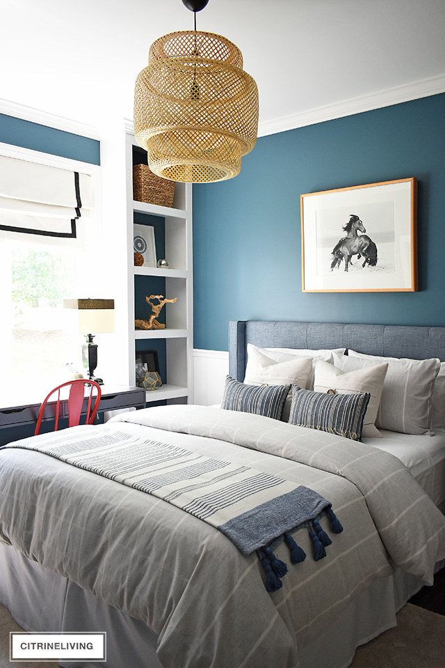 Modern coastal teen bedroom with large-scale woven bamboo chandelier, striped bedding and pillows, modern decor on open shelves.