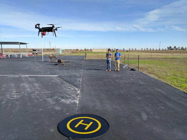 Two students stand in the background of a concrete lot, holding a remote control. In the foreground, a flying UAV approaches a landing marker.