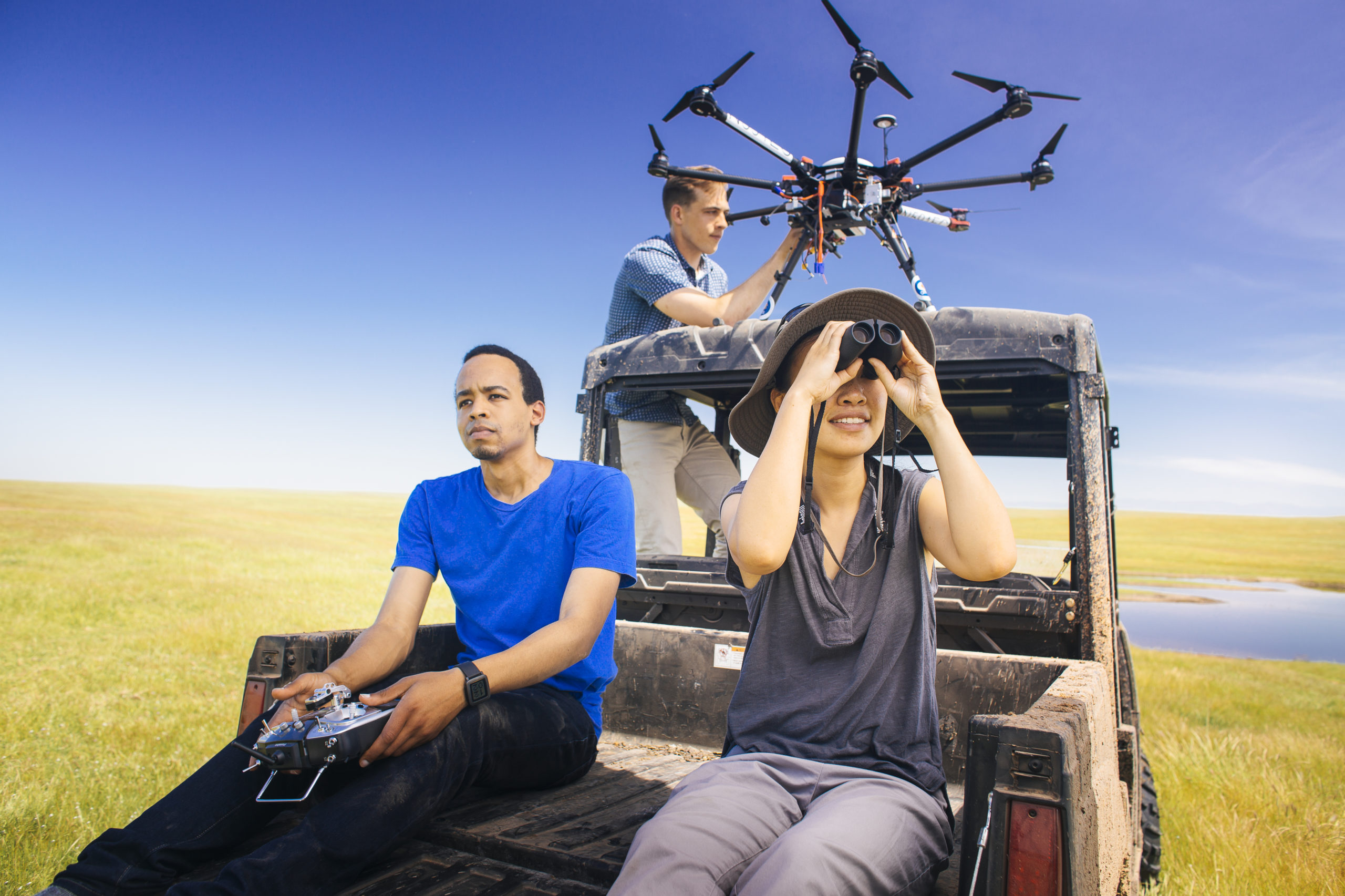 Two students sit in the back of a muddy all-terrain vehicle in a marsh, while another student stands in the cab. One of the students in the ATV bed is holding a UAV controller, and the other is looking through a pair of binoculars. The standing student is holding a large UAV with eight rotors.