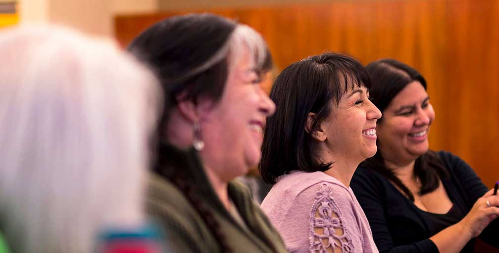 Side shot of three women smiling in a meeting